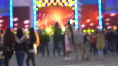 Blurred people dancing at live show against outdoor stage. 4K background bokeh Stock Footage
