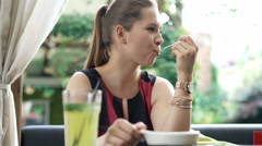 Cute young woman eating tasty dessert in cafe Stock Footage