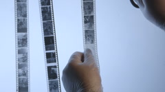 Film processing photographer cutting 35mm black and white negatives Stock Footage