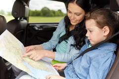 Happy family with travel map driving in car Stock Photos