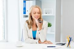 Businesswoman using voice command on smartphone Stock Photos