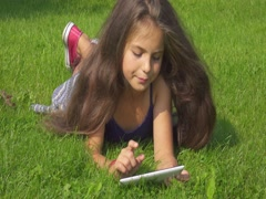 Young nice girl laying on grass watches and taps something on her smartphone. Stock Footage