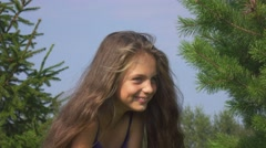 Young nice girl outdoors smiles and laughs coquettishly before camera. Stock Footage