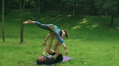 Young woman and man performing acrobatic yoga. Slow motion. HD Stock Footage
