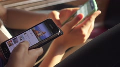 Two friends, young girls watching something on smartphones, close up, authentic. Stock Footage