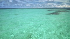 Clear turquoise water with some dark stones underneath, tilt up to blue sky Stock Footage