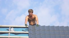 Man working at construction of house, screwing and installing metal tile roof. Stock Footage