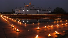 Maha Devi temple with lit candles around pond,Lumbini,Nepal Stock Footage