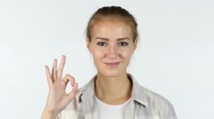 OK sign by a young girl in front of white background Stock Footage