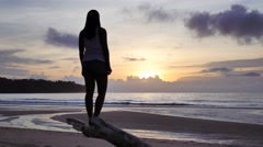 Woman gazing at the horizon and the wonders of a sunset at a paradise beach Stock Footage
