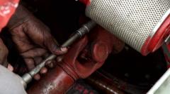 An African worker screwing a bolt. Stock Footage