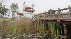 Bridge over pond to buddhist temple,Lumbini,Nepal Stock Footage