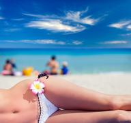 Woman in white swim suit relaxing on tropical beach Stock Photos