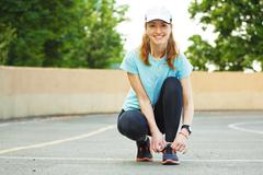 Beautiful young woman tying her laces before a run. Stock Photos