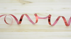 Red curled ribbon on wood table Stock Footage