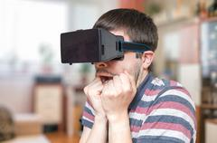 Young man is wearing 3D virtual reality glasses and is scared. Stock Photos