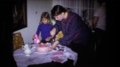 1973: a woman cutting a pink birthday cake as a child attempts to put on a party Stock Footage