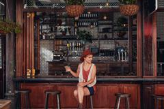 Attractive young woman sitting alone at a cafe Stock Photos