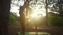 Girls practicing yoga stretching at sunset in forest Padahastasana Slow motion Stock Footage