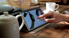 Man visits iWatch website on tablet pc in a cafe Stock Footage