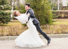 Groom holding bride in dance pose on wedding day Stock Photos