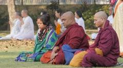 Pilgrims and monks meditating at cremation stupa,Kushinagar,India Stock Footage