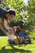 Father helping his son in garden to take his first step of life Stock Photos