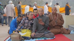 Monks and pilgrims praying with smartphone at Parinirvana Stock Footage
