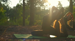 Girls practicing yoga at sunset in forest Dhanurasana Slow motion Stock Footage
