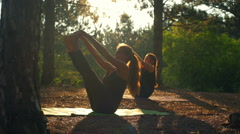 Girls practicing yoga at sunset in forest Paripurna Navasana slow motion Stock Footage
