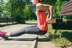 Woman in sportswear doing exercise on triceps on a park bench Stock Photos