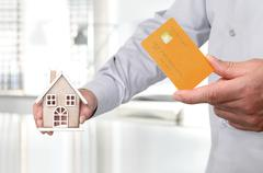 Hands with house and credit card, buy house concept Kuvituskuvat
