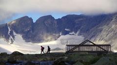 Mountain scenery bridge hikers walking silhouette beautiful clouds blue sky Stock Footage