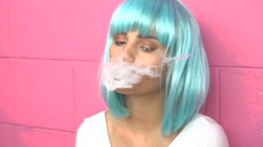Sexy young girl in modern futuristic style with blue wig smoking e-cigarette Stock Footage