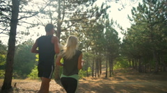 Sportive couple jogging along path in forest Slow motion Back view Stock Footage