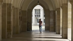 Girl with a mobile phone in an ancient colonnade Stock Footage