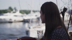 Young girl sitting on terrace of restaurant at seafront. Speaking with someone Stock Footage