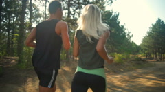 Young sportive couple jogging along path in forest Slow motion Back view Stock Footage