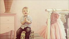 Cute one year old baby sitting on the ottoman in the nursery. Child claps. Stock Footage