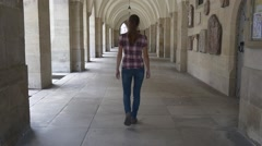 Woman walks through the colonnade of the Gothic cathedral Stock Footage