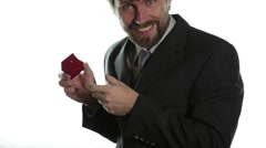 Bearded man in a business suit gives a ring in the red box and expresses Stock Footage
