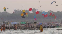 Pilgrims bathing and boats with flags,Allahabad,Kumbh Mela,India Stock Footage