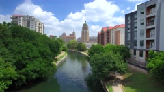 Aerial view of San Antonio riverwalk by skyline under sunny blue sky Stock Footage