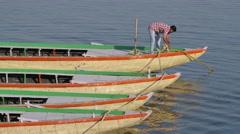 Man tying boat on Ganges,Varanasi,India Stock Footage