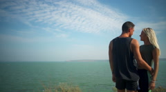 Beautiful sportive couple rejoicing looking at sea landscape Slow motion Stock Footage