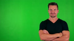 Young handsome caucasian man smiles to camera with folded arms - green screen Stock Footage
