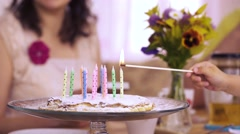 Few hands lighting long matches candles birthday homemade pie Stock Footage