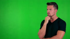 Young handsome caucasian man thinks about something - green screen - studio Stock Footage