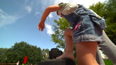Mother play with her little daughter at playground. Child learns to climb up Stock Footage