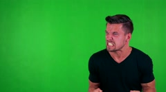 Young handsome caucasian man is angry - green screen - studio Stock Footage